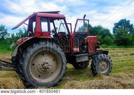 Old Red Tractor In The Field During The Haymaking Season, Pressing Hay On Bales, Forage Harvesting.2