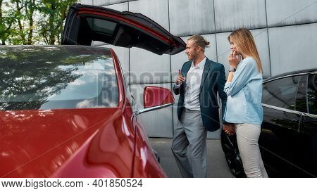Young Caucasian Couple Examining New Car In Dealer Showroom While Standing Near Auto Holding Hands,