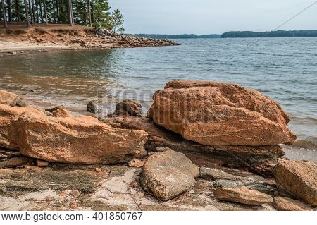 Drought Conditions At The Lake Causing The Rocky Shoreline With Large Rocks And Boulders Exposed Wit