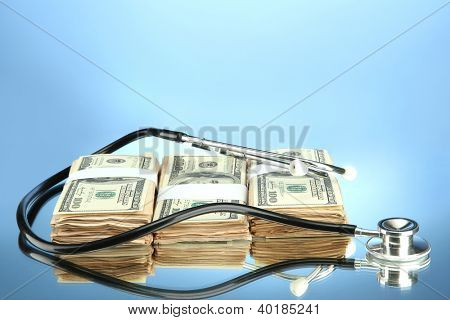 Healthcare cost concept: stethoscope and dollars on color background