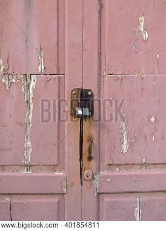 Rusty Padlock On Pink Wooden Door With Uncorked Paint. Old Metal Padlock On A Uncorked Wooden Door.
