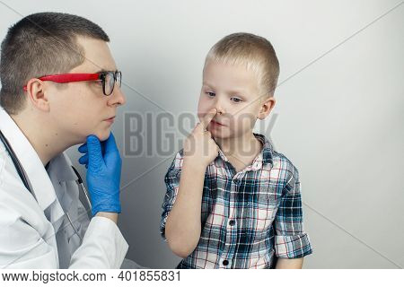 The Otolaryngologist Examines The Boy Nasal Passages. Painful Sensations In The Nose, Polyps, Adenoi