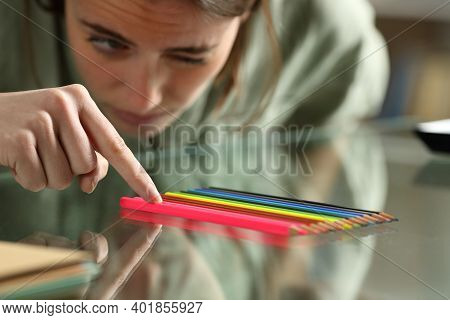 Obsessive Compulsive Woman Aligning Up Pencils Accurately On A Glass Table