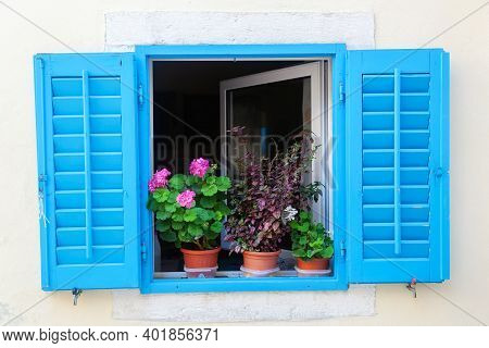 Picture Of A Decorative Window With Blue Shutters And Flower Pots