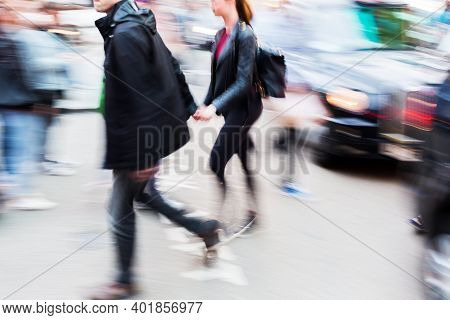 Couple Crossing A City Street In Motion Blur
