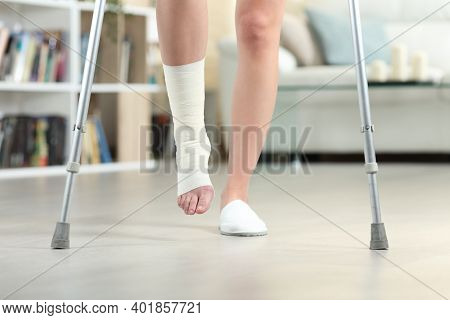 Front View Close Up Of A Disabled Woman Walking With Crutches And Sprained Bandaged Ankle At Home