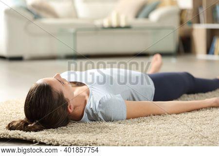 Woman Relaxing Doing Savasana Yoga Pose Lying On A Carpet At Home