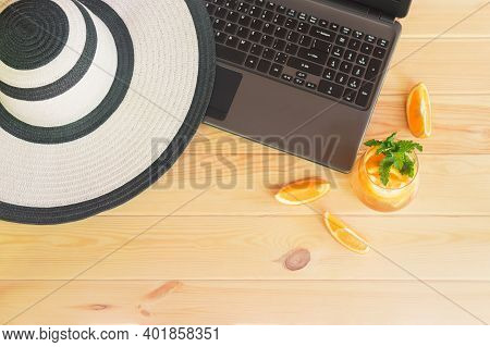 Summer Hat, Laptop And Orange Lemonade On Wooden Table. Summer Holidays Concept. Top View.