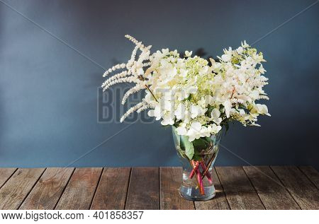 White Beautiful Astilbe And Hydrangea Flowers In Glass Vase On Wooden Table. Selective Focus. View W