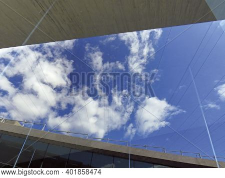 Modern Architecture Detail Under Blue Sky With White Clouds And Light Flares. Close Up Exterior View