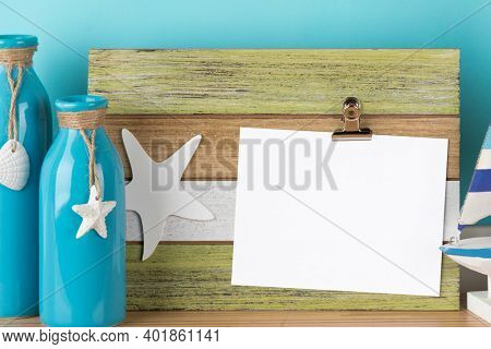 Greeting card mockup on rustic wooden clipboard. Maritime decoration design template with vases, starfish and sea shell ornaments. Blank area isolated with clipping path.