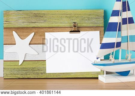 Greeting card mockup on rustic wooden clipboard. Maritime decoration design template with starfish ornament and toy sail boat. Blank area isolated with clipping path.