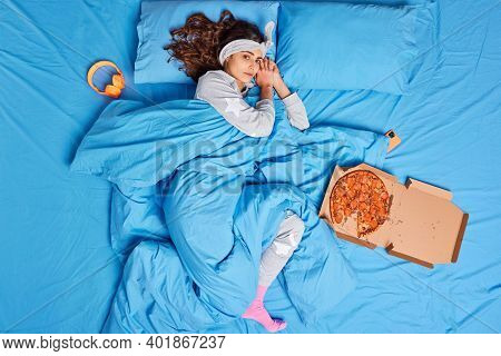 Lovely Brunette Woman Rests On Comfortable Bed Wakes Up Late Dressed In Soft Nightwear Eats Pizza Be