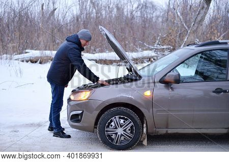 Car Repair On The Road In Winter. A Young Man Is Trying To Fix A Car Breakdown Under The Soot On The
