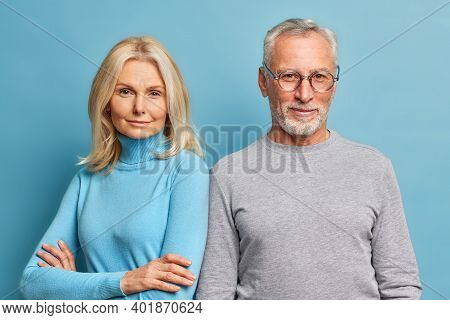 Serious Self Confident Blonde Pretty Woman Stands With Arms Folded Near Her Husband Pose For Making