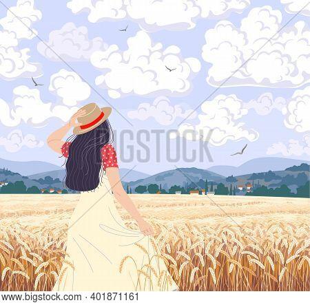 Young Woman Enjoys The Wheat Field Scenery. Dreamy Girl In Straw Hat Walking Among Ripe Wheat Ears.