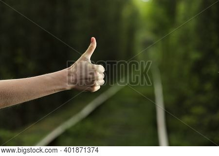 Like It. Thumb Up With Natural Bokeh Background Of Leafy Green Forest, Hand With Thumb Up In The Wil