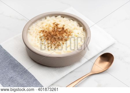 Creamy Rice Pudding With Cinnamon In Bowl On White Marble Table. Typical Spanish Dessert