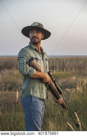 Ranger In A Hat Stands In A Field With A Gun
