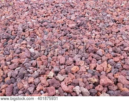 Reddish Volcanic Gravel Background. Red Volcanic Stone, Porous In Appearance, Of Different Shapes An