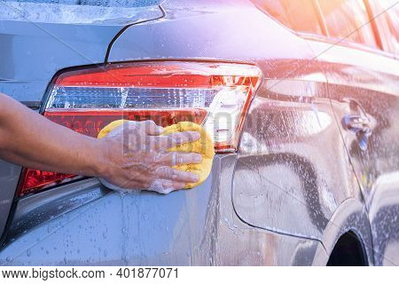 Close Up Man's Hand Using Sponge And Foam To Washing Taillight Modern Car In Perspective Side View