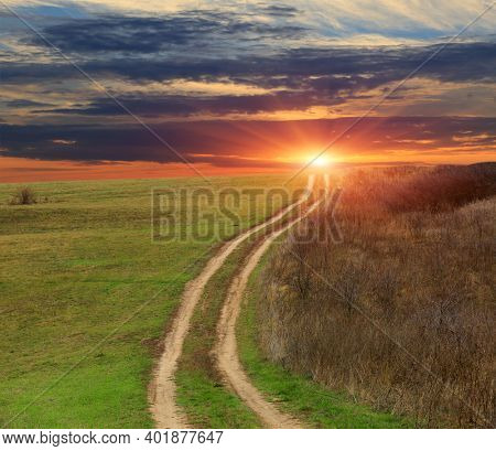 Landscape with countryside road across green meadow to sunset