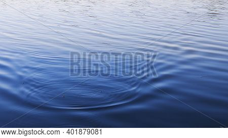 Tranquil Lake Water With Smooth Ripple Surface And Blurry Reflection. Blue Wavy Water Background Wit
