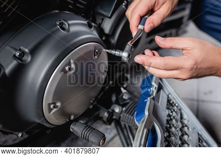 Cropped View Of Mechanic Unscrewing Cap Of Motorbike Gearbox With Socket Wrench