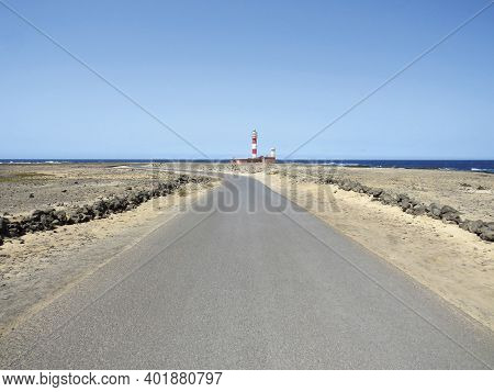 Lonely Paved Road In Arid Area Towards Red And White Maritime Lighthouse Under Blue Ocean And Sky. L