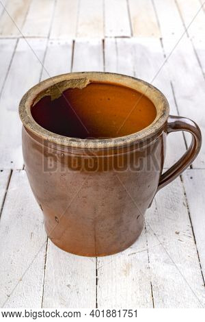 Clay Pot On A Wooden Table. A Container Used In The Kitchen For Pickling Cucumbers. Light Background