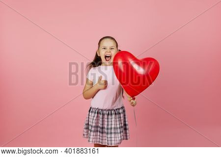 Close-up Enthusiastic Ecstatic Rapturous Girl In Pink Dress Holds Red Balloon In The Shape Of Heart
