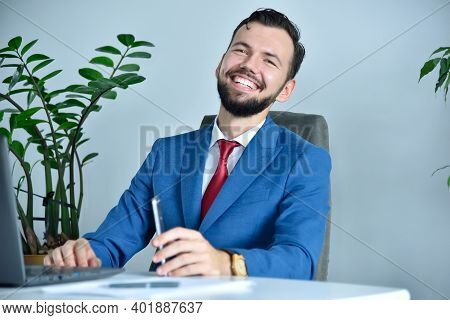 Happy Bearded Businessman Sitting In Modern Office. Occupation And Worker Concept.
