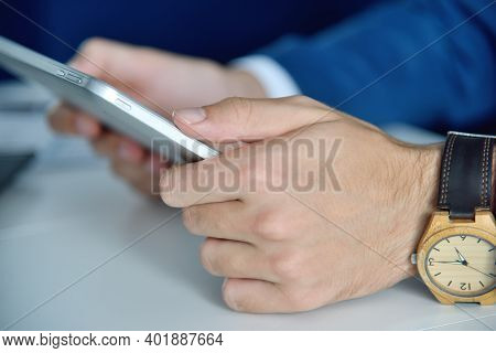 Close Up Of Hands Using Tablet Computer With Business Report. Business And Financial Success Concept