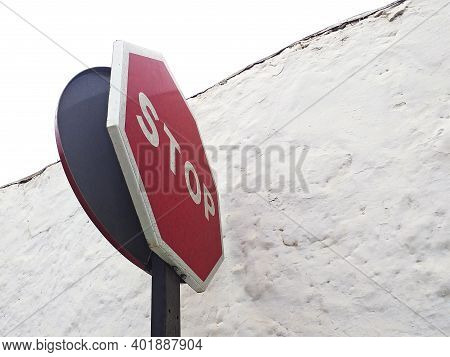 Down Angle View Of Stop Sign Against White Rough Concrete Wall. Side View Of A Stop Road Sign. Regul
