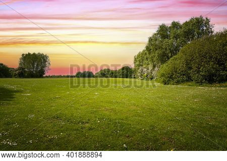Field of green grass and beauttiful sky at sunset