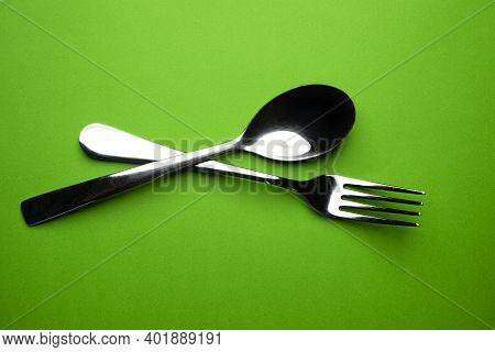A Fork And A Spoon On A Green Surface