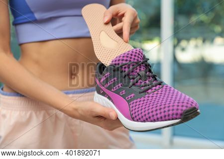 Woman Putting Orthopedic Insole Into Shoe Indoors, Closeup. Foot Care