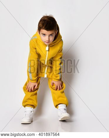 Studio Full Length Portrait Shot Of Little Boy Wearing Yellow Fleece Warm Jumpsuit Standing Touching