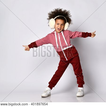 Fashion Advertising In Childhood. African American Girl Sings And Poses In Warm Headphones And Sport