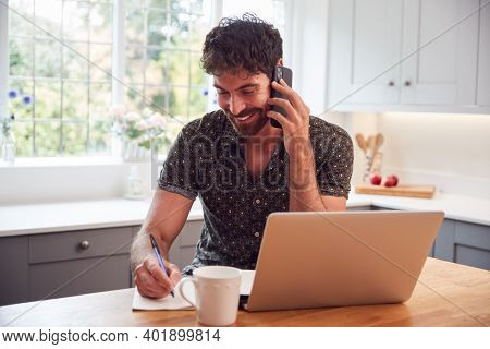 Man In Kitchen With Mobile Phone Working From Home Using Laptop During Health Pandemic