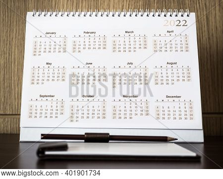 Desktop Calendar 2021 With Blank Note On Wooden Desk In Private Office