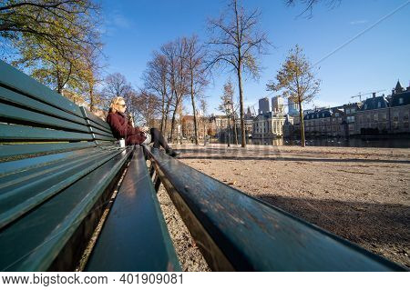 The Hague, The Netherlands - November 9, 2020: A Young Blonde Woman Is Eating Lunch On A Park Bench