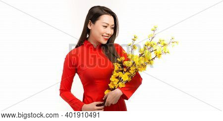 Asian Woman With Vietnamese Traditional Dress Ao Dai Holding Blossom Flower For Decorations. Lunar N