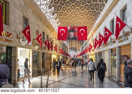Bursa, Turkey - October 14, 2019 : Unidentified Turkish people shopping inside the modern and renewed part of Grand Bazaar in Bursa city. Turkish flags and Mustafa Kemal Ataturk portrait on the wall