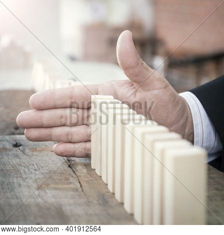 Management Concept: Manager Hand Stopping The Domino Effect On Office Background
