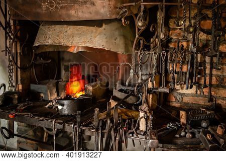 Interior Of Blacksmith Forge With Tools Hanging On Wall And Anvil And Hammer Ready To Be Used. Furna