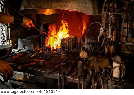 The Blacksmith Holds Billet Over Hot Coals In Clay Oven. Blacksmith Heating Iron Metal Sword Manufac