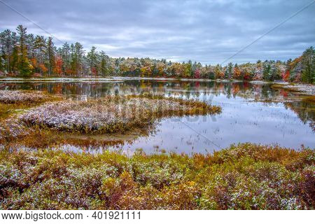 Michigan Autumn Landscape. First Snow And Vibrant Fall Colors At A Small Wilderness Lake In Tahquame