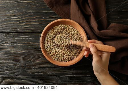 Female Hand Holds A Spoon With Legumes Over A Bowl Of Legumes On Wooden Background