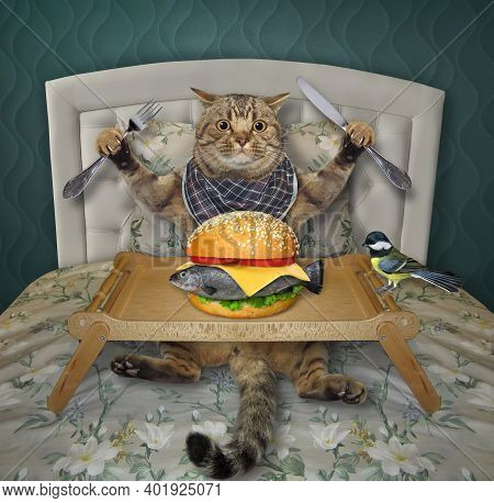 A Beige Cat Is Eating A Big Fresh Fish Burger From A Wooden Tray In The Bed At Home.